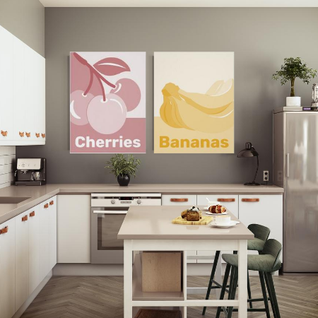 pastel kitchen wall decor showing monochrome poster prints of cherries in reddish pastel hues, and bananas in yellow pastels in a white kitchen