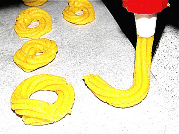 pipe bag forming spritz cookies on the baking pan