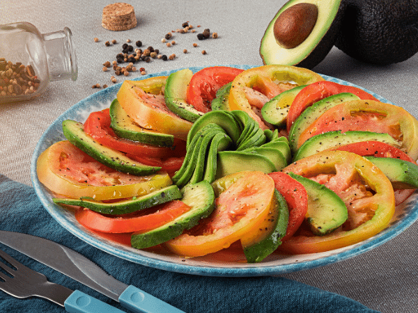 tomato and avocado salad, arranged with circular layerd alternating thin tomato and avocado slices