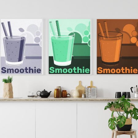 white dining area decorated with digital art poster prints showing a smoothie tumbler with straw and a bowl of fruits, one print shows monochrome pastel blue, the second in green, the third in orange